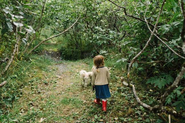 Little girl and her dog walking on a nature trail