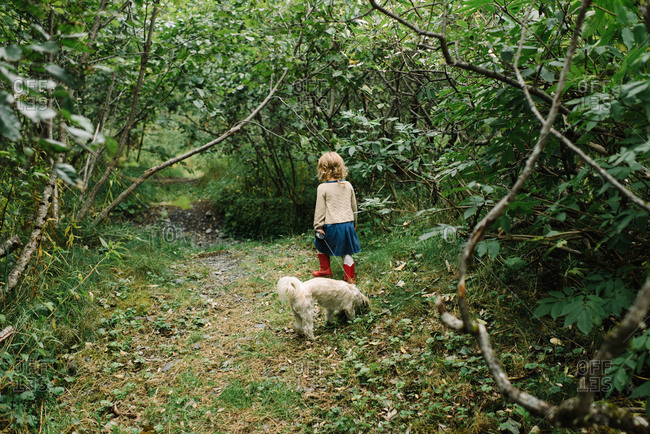 Little girl walking her dog on a nature path