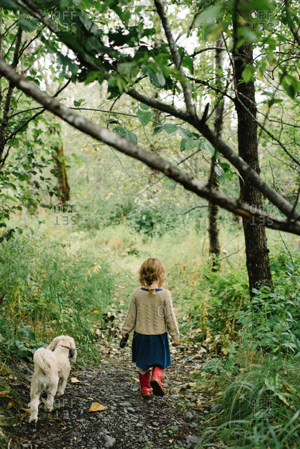 Girl and her dog walking on a rocky trail