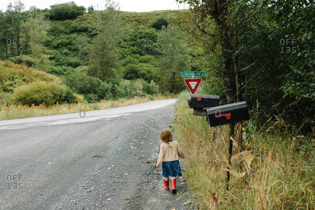 Little girl walking near mailboxes on a rural road