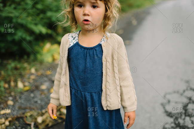 Little girl standing on a paved country road