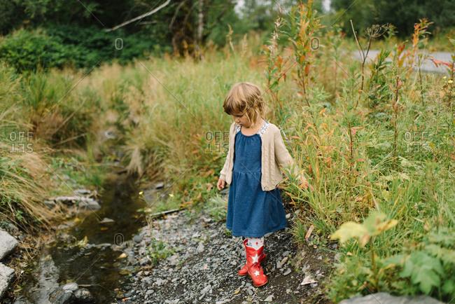 Little girl standing in gravel near a ditch