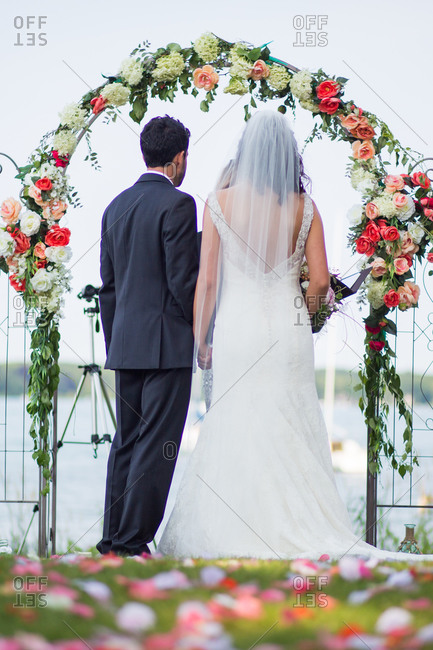 Back view of couple during wedding ceremony under arch decorated with roses and hydrangea