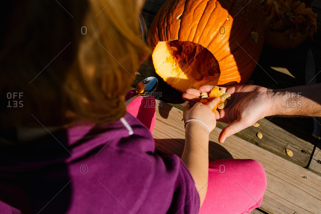 Girl scooping pumpkin seeds and putting them in her father's hand