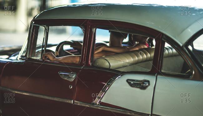 Couple inside a vintage car in Cuba