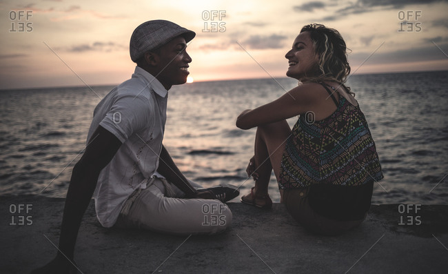 Couple sitting oceanfront at sunset in Cuba