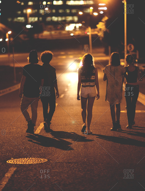 Teens walking on a road at night