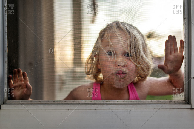 Girl making a funny face at a window