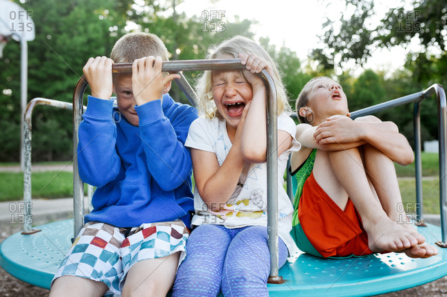 Children pretending to be scared on a merry-go-round