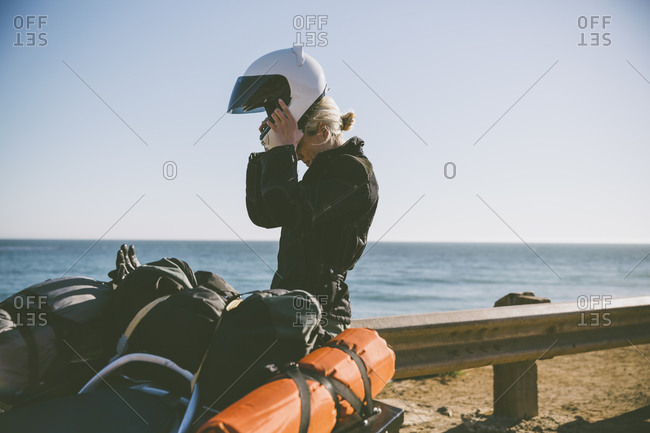 Motorcyclist putting her helmet on