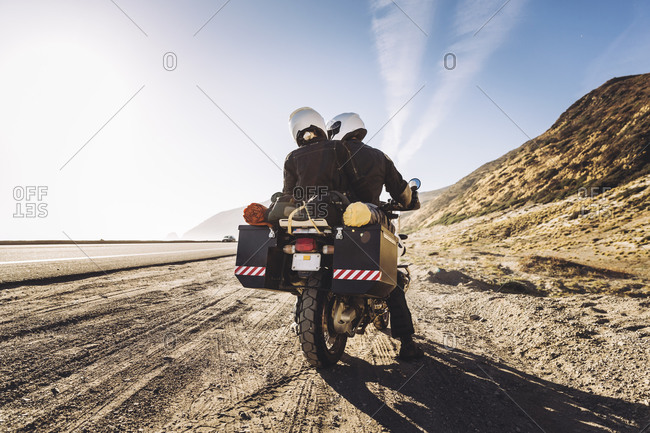 Couple on a motorcycle stop on side of the road
