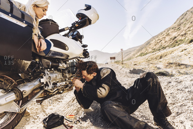 Couple repairing their motorcycle on the side of the road