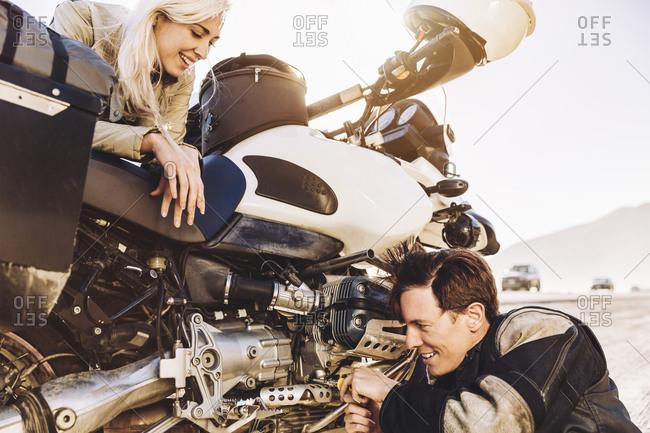 Woman watching her boyfriend repair their motorcycle