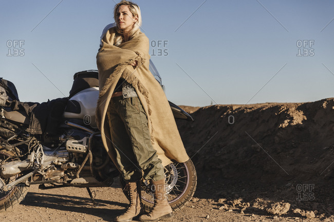 Woman wrapped in a shawl next to a motorcycle
