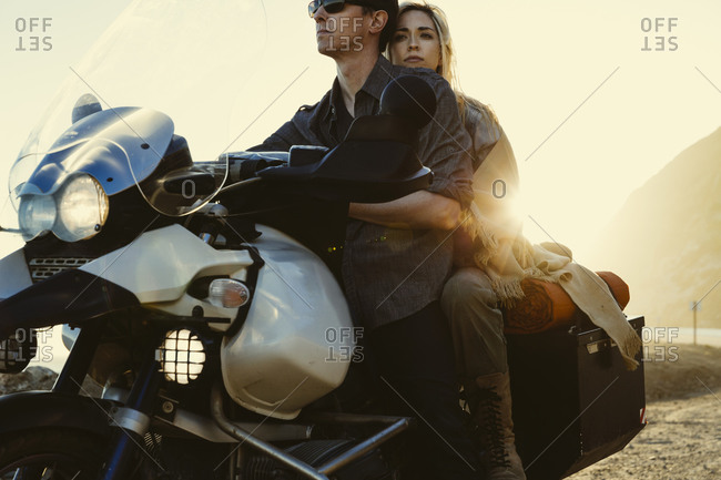 Couple sitting on their motorcycle at sunset