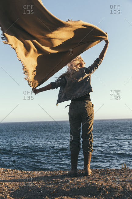 Woman standing on the shore with a blanket