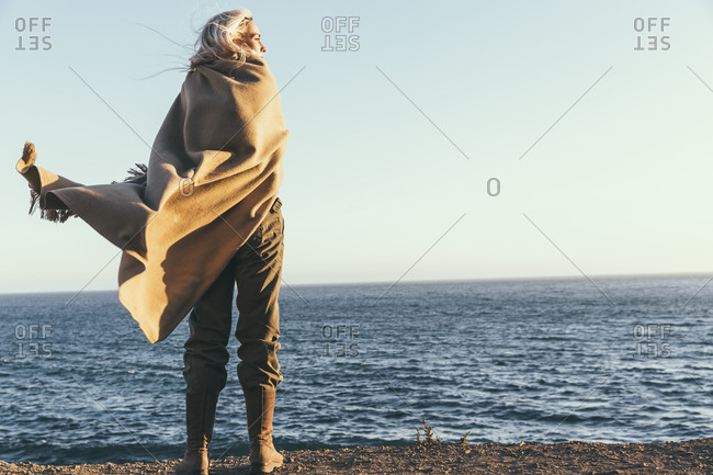 Woman wrapped in a shawl on the beach