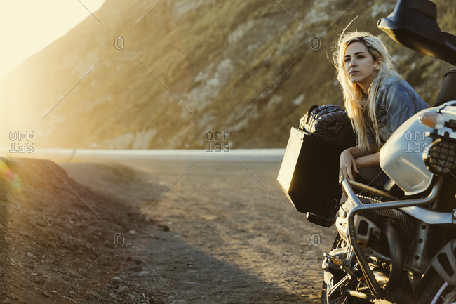 Woman and a motorcycle at sunset