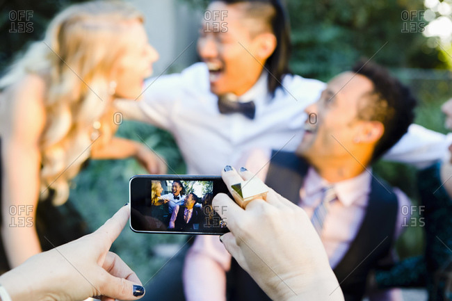 Friends taking pictures at a party with a smartphone