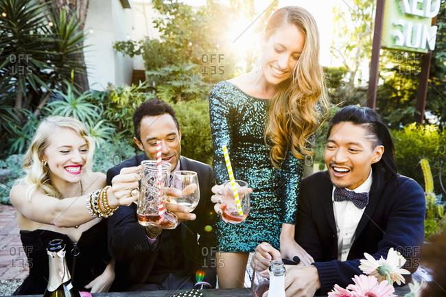 Friends clink cocktail glasses together