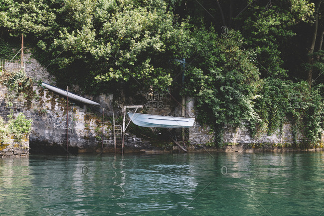 Boat hanging above a lake near an old stone wall