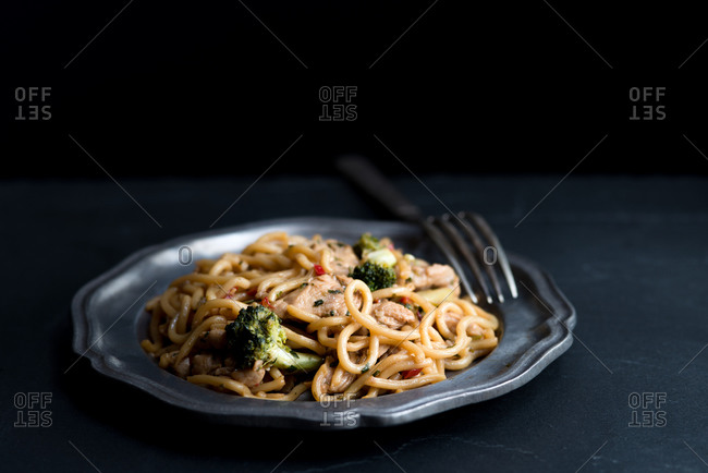 Asian noodles with broccoli on a metal plate