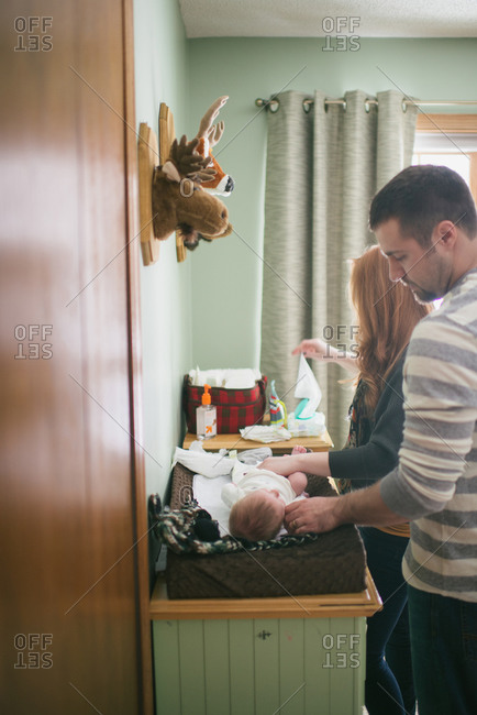 Parents changing baby's diaper
