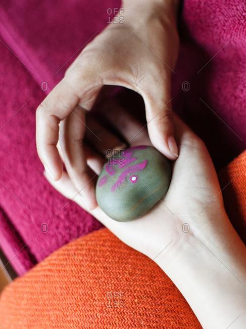 Woman receiving Tibetan hand massage with stone