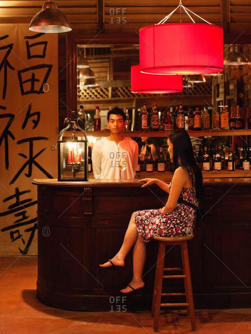 A woman drinks a glass of wine hotel bar, Langkawi, Malaysia