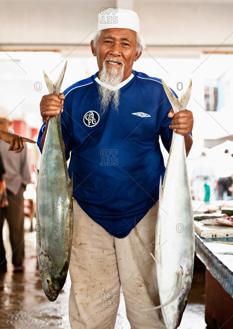 Dungun, Malaysia - March 18, 2009: Portrait of a fish monger with fish in Malaysia