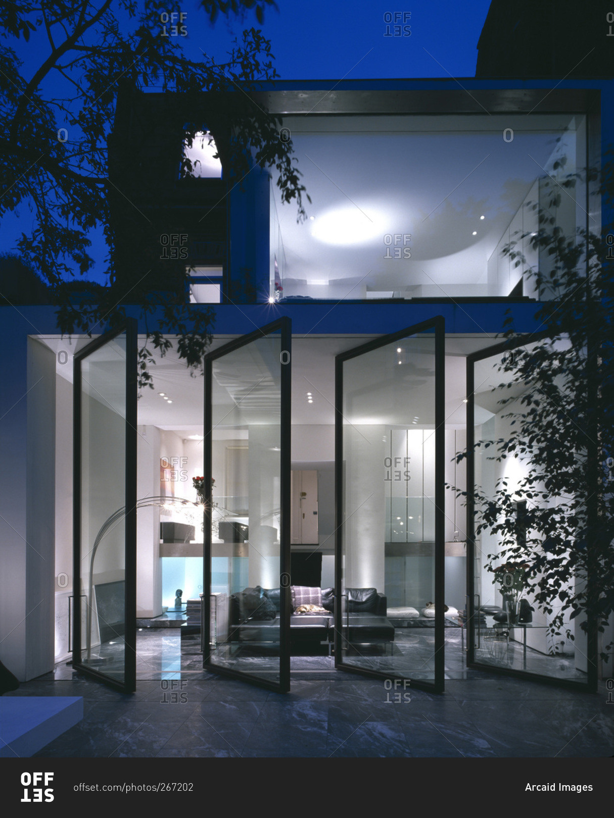 Rear of a refurbished modern house with an open glass wall Opening glass walls