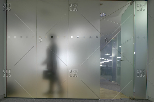 Silhouette of a man through a frosted glass wall in a modern office