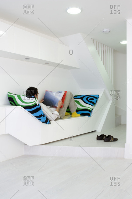 Man reading a book in a modern townhouse in London