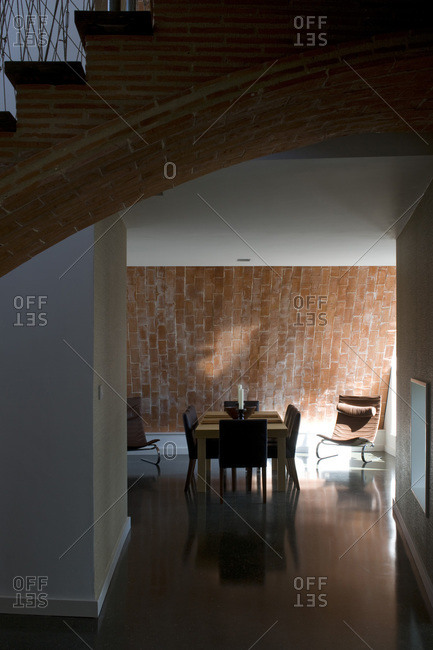 Open plan dining room and exposed brick staircase in a zero carbon house