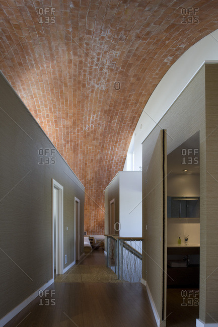 Open bathroom door in a hallway with an exposed brick ceiling in a zero carbon house