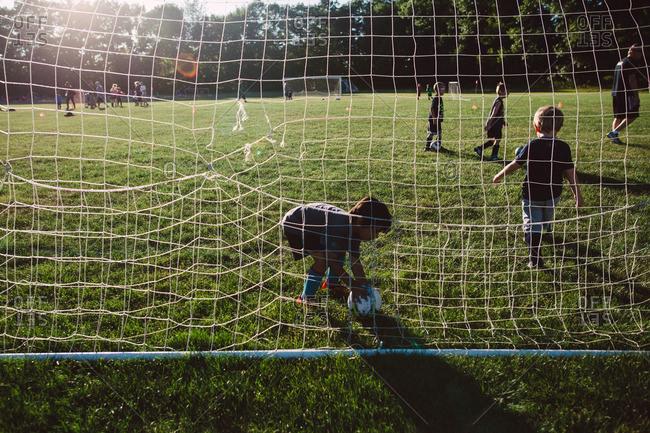 A goalie picks up a soccer ball