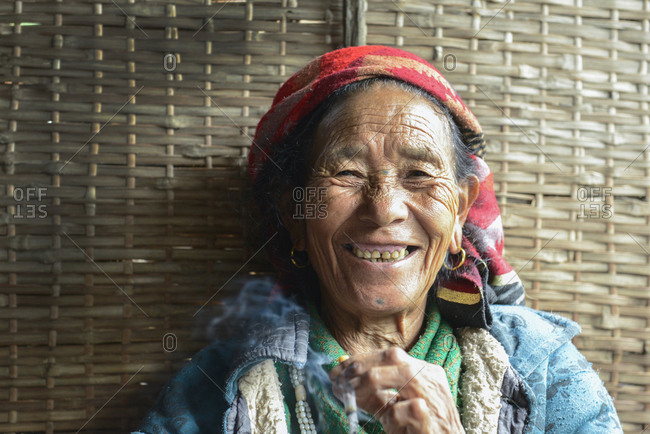 Nepali woman smiling and smoking a cigarette
