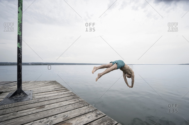 Man diving into a lake from a dock