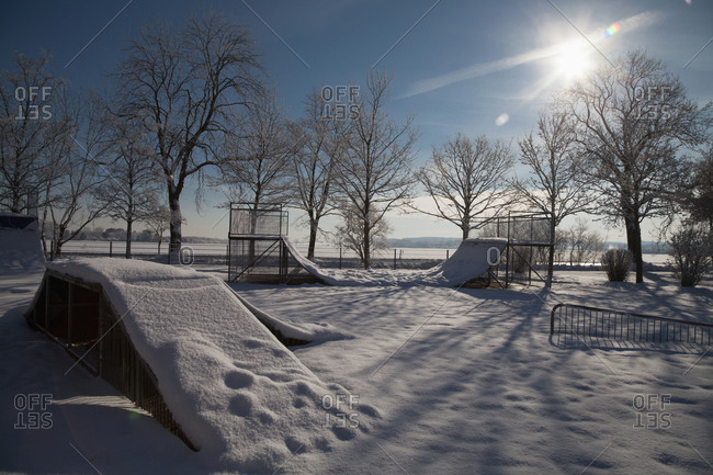 Snow-covered skate park near a frozen lake