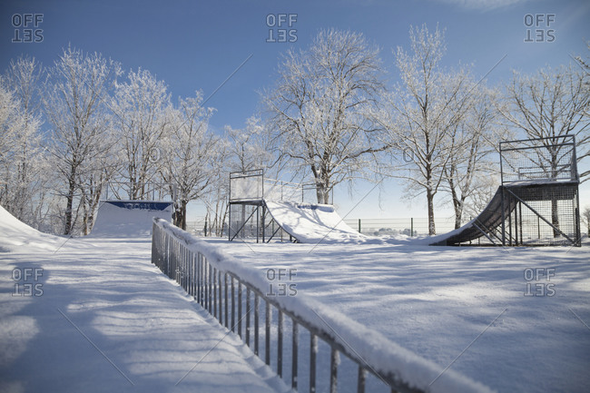 Snow-covered ramps at a skate park near a lake