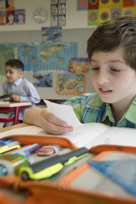 Little boy at his school desk reading a note