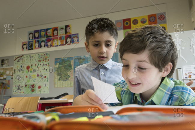 Two boys looking at a note in a classroom