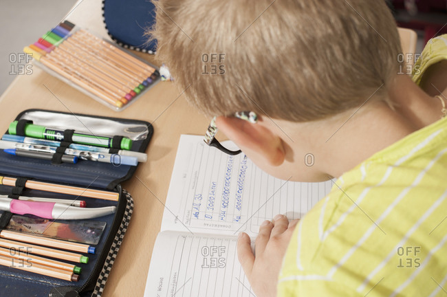 Little boy writing in a notebook at school