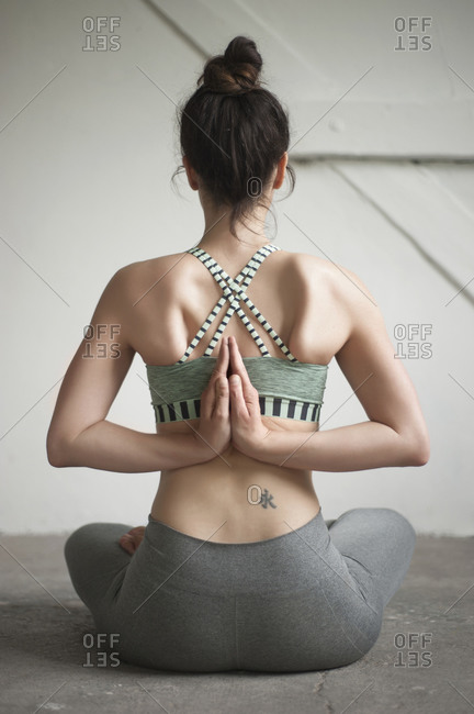 Woman seated in a reverse prayer yoga pose