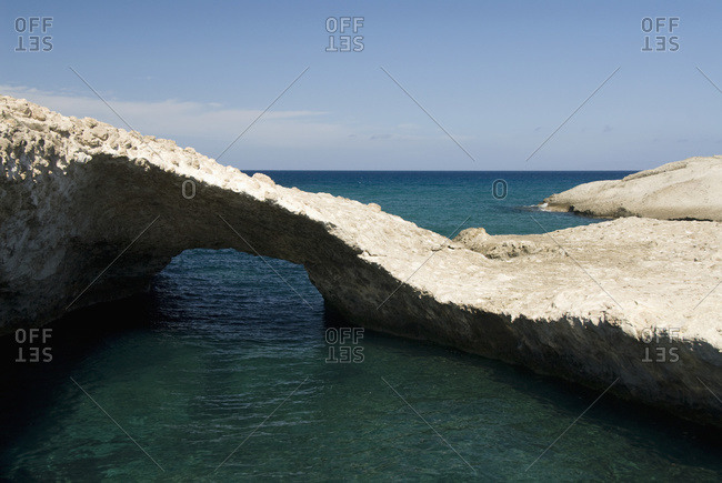 A tranquil pool of water and unique rock formation off the coast, Karpos, Island Of Milos, Greece