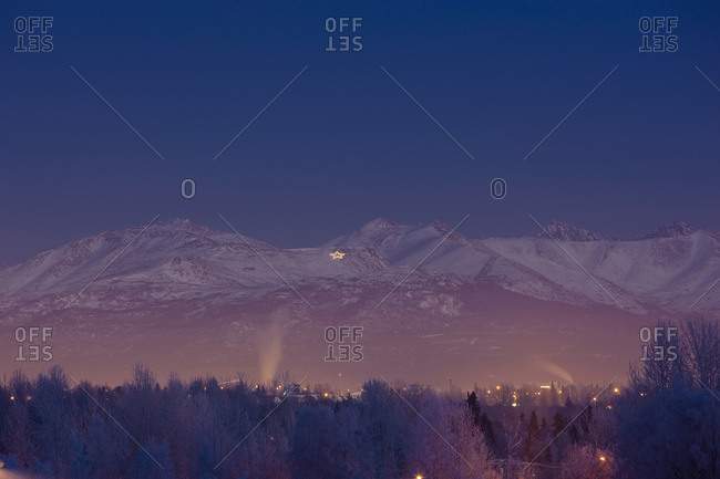 View Of The Chugach Mountains At Twilight With The Site Summit Star Visible Atop Mount Gordon Lyon During Winter, Anchorage, South-central Alaska