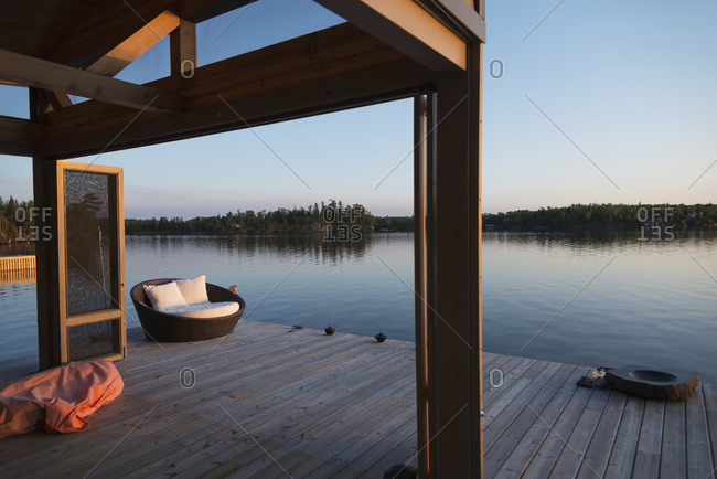 A wooden dock with a cushioned seat along the water's edge, Lake Of The Woods, Ontario, Canada