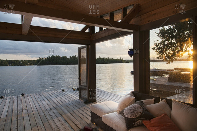 Covered patio on a wooden deck on the water's edge at sunset, Lake Of The Woods, Ontario, Canada