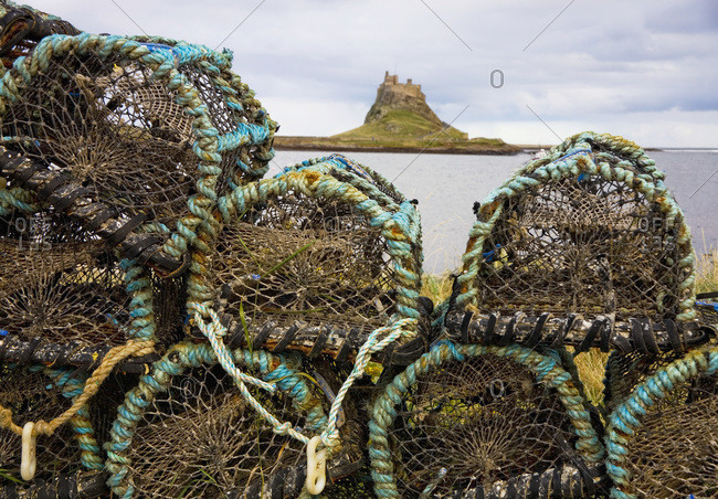Traps piled on the water's edge with lindisfarne castle in the distance, Lindisfarne, Northumberland, England