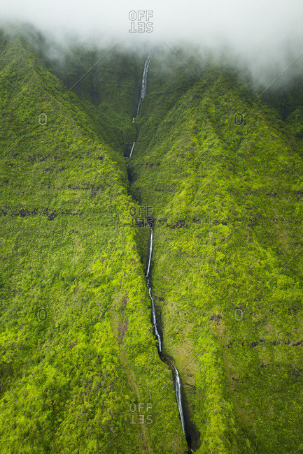 A stream flowing down a lush green mountainside with low lying cloud, Hawaii, United States Of America